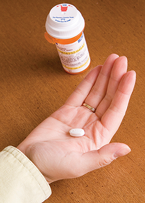 Woman's hand holding pill with prescription pill bottle nearby.